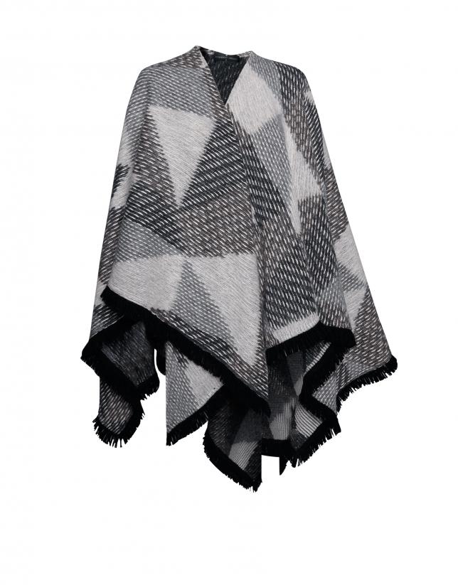 Poncho tricot à motifs géométriques gris.