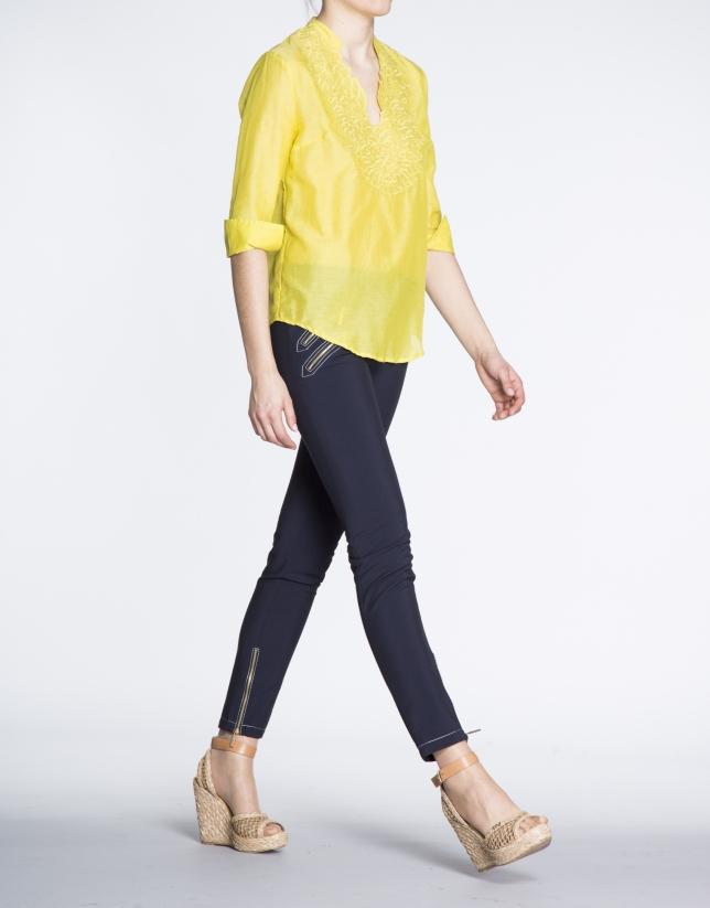 Blusa de seda amarilla con escote bordado a tono.