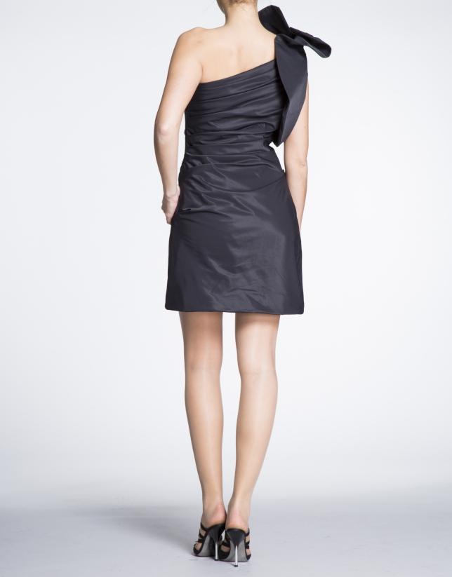 Robe courte aymétrique noire avec volant sur l'épaule.