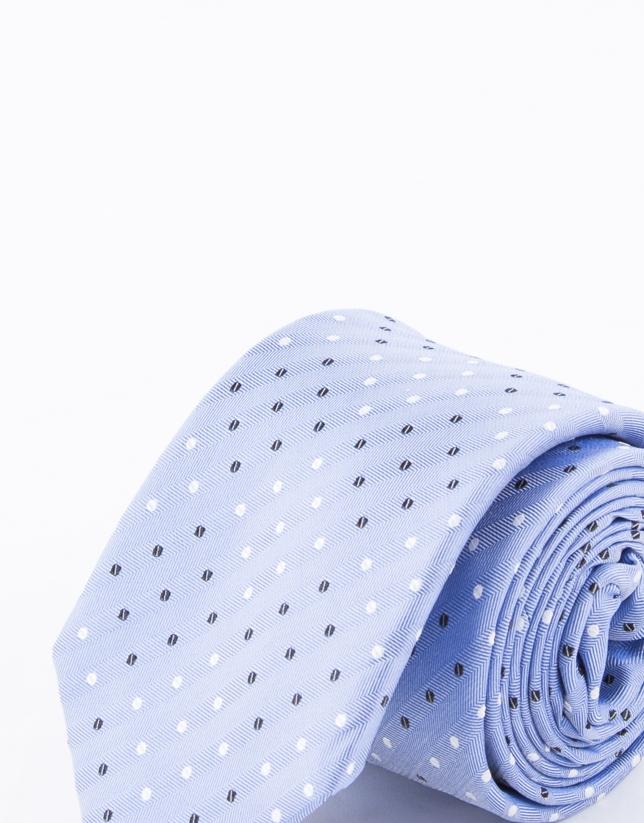 Cravate à pois blancs et bleu marine sur fond bleu