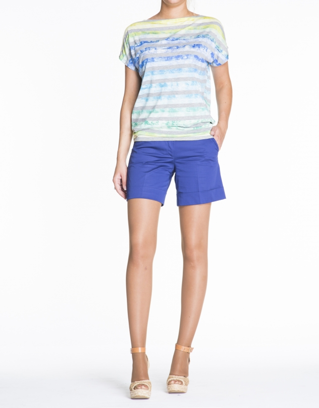 Camiseta floja estampada franjas grises sobre azules, amarillos y verdes.