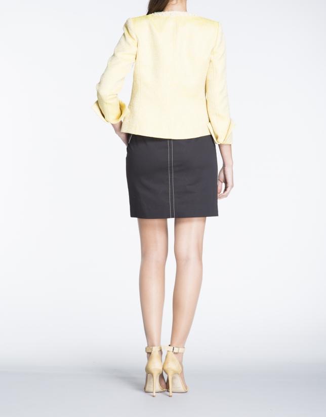 Chaqueta corta de tejido labrado amarillo.