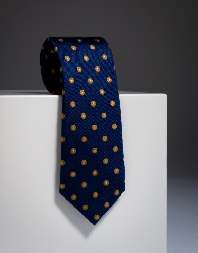 Corbata de seda color azul con lunares dorados y topo crudo en medio.