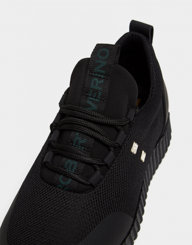 Black running shoes with green logo