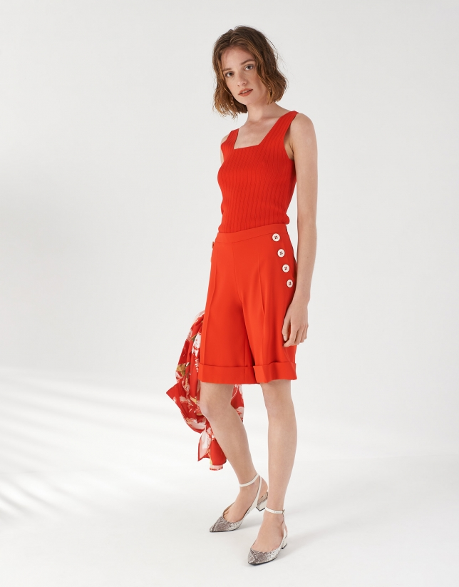 Red shorts with decorative row of buttons