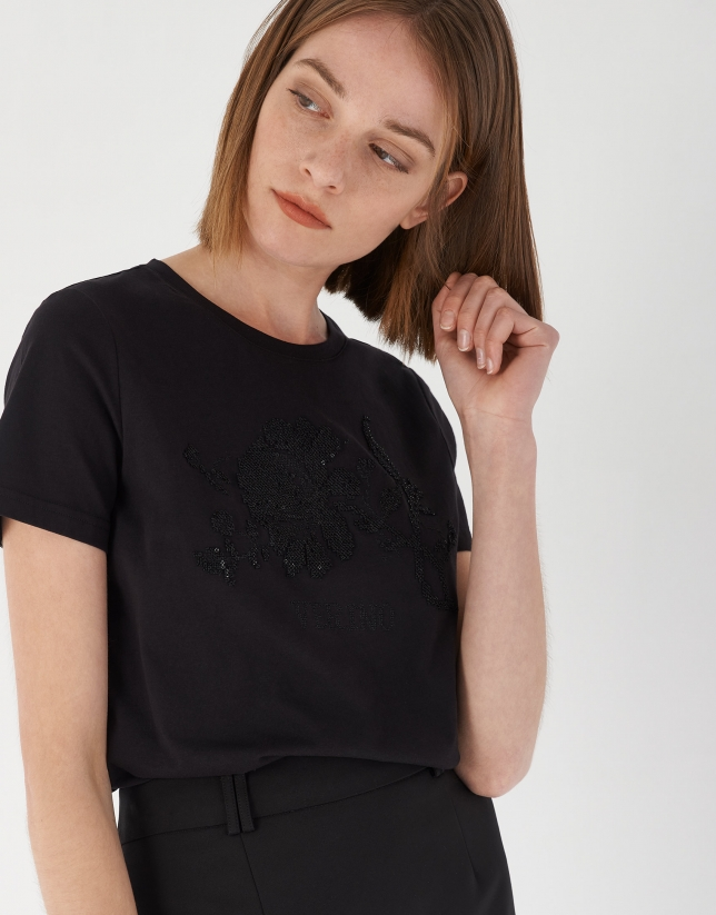 Black top with short sleeves and cross-stitched embroidery