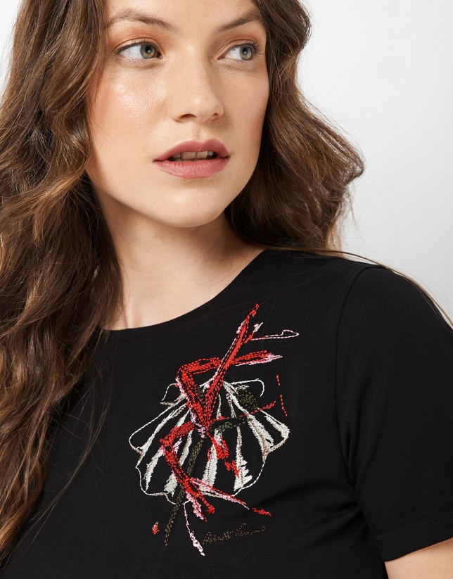 Black top with an embroidered flower on the chest